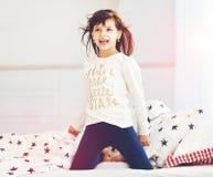 愉快的苍劲的女孩在早晨太阳光醒,唱歌在卧室 免版税库存照片