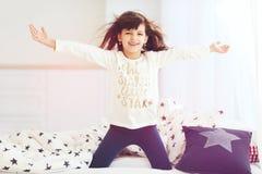 愉快的苍劲的女孩在早晨太阳光醒,唱歌在卧室 免版税库存图片