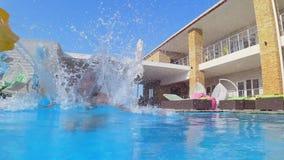 愉快的苗条女孩到有可膨胀的圆环下潜的游泳衣里在昂贵的手段的水池在暑假时 影视素材