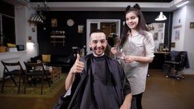 愉快的英俊的人在看他自己的理发店在大镜子在发型以后 女性理发师展示 股票视频
