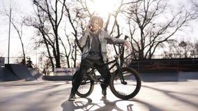 愉快的英俊的十几岁的男孩画象有dreadlocks的,使用手机,当骑BMX自行车,微笑,传讯时 股票视频