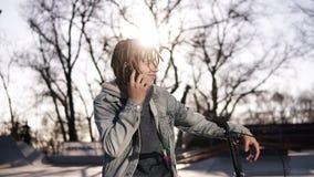 愉快的英俊的十几岁的男孩画象有dreadlocks的,使用手机,当骑BMX自行车,微笑,传讯时 影视素材