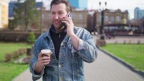 愉快的英俊的商人谈话在巧妙的电话在度假在欧洲遥远的4G Wi-Fi互联网和旅行的 股票录像