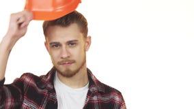 愉快的英俊的年轻建筑工人微笑的佩带的安全帽 股票录像