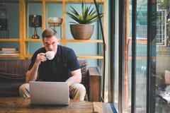 愉快的英俊的年轻人饮用的咖啡 免版税库存照片