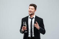 愉快的英俊的年轻商人饮用的香槟和指向在您 免版税库存图片