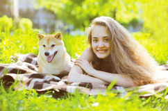 愉快的获得女孩和的狗在草的乐趣 免版税库存图片