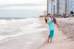 愉快的获得小孩男孩和的母亲乐趣在海滩海洋和在风暴日 免版税库存图片