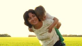 愉快的获得母亲和她的小的儿子乐趣户外 美丽的家庭妈妈和她的亲吻儿童的男孩一起拥抱和 股票录像