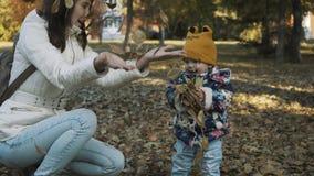 愉快的获得母亲和的女儿一起使用与秋叶和乐趣 嬉戏的女孩和她的母亲投掷了叶子 股票录像