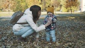 愉快的获得母亲和的女儿一起使用与秋叶和乐趣 嬉戏的女孩和她的母亲投掷了叶子 股票视频