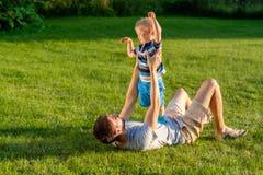 愉快的获得父亲和的儿子乐趣室外在草甸 库存照片