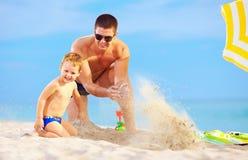 愉快的获得父亲和的儿子在海滩的乐趣 免版税图库摄影