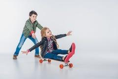 愉快的获得男孩和的女孩与滑板的乐趣 免版税库存照片