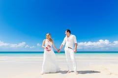 愉快的获得的新娘和新郎在一个热带海滩的乐趣 婚姻  库存照片
