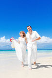 愉快的获得的新娘和新郎在一个热带海滩的乐趣 婚姻  免版税库存照片