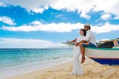 愉快的获得的新娘和新郎在一个热带海滩的乐趣 婚姻  免版税库存图片