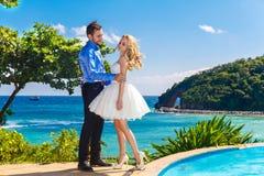 愉快的获得的新娘和新郎在一个热带海滩的乐趣 免版税库存照片