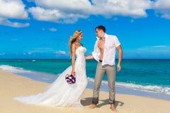 愉快的获得的新娘和新郎在一个热带海滩的乐趣 免版税库存图片