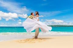 愉快的获得的新娘和新郎在一个热带海滩的乐趣 库存图片