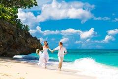 愉快的获得的新娘和新郎在一个热带海滩的乐趣 免版税图库摄影