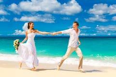 愉快的获得的新娘和新郎在一个热带海滩的乐趣 库存照片