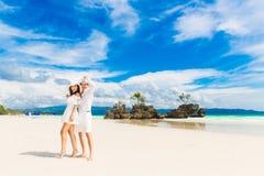 愉快的获得的新娘和新郎在热带海滩的乐趣 婚姻 免版税库存照片
