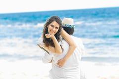 愉快的获得的新娘和新郎在热带海滩的乐趣 婚姻 图库摄影