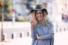 愉快的行家妇女佩带的帽子和玻璃在城市夏天 免版税库存图片