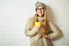 愉快的行家时尚女孩在与杯子的冬天 库存照片