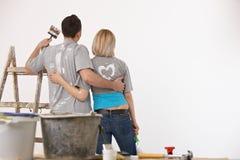 愉快的被绘的白色墙壁夫妇站立的前面  免版税库存图片