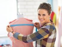 愉快的裁缝妇女与礼服一起使用 免版税库存照片