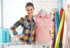 愉快的裁缝妇女画象在时装模特附近的 免版税库存图片