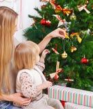 愉快的装饰圣诞树的母亲和她的女儿 免版税库存照片