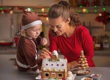 愉快的装饰圣诞节曲奇饼房子的母亲和婴孩 免版税库存图片