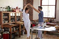 愉快的西班牙夫妇跳舞在厨房里早晨 免版税图库摄影