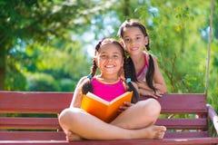 愉快的西班牙姐妹在夏天公园 免版税图库摄影