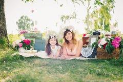愉快的说谎在毯子的母亲和女儿户外在一个晴朗的夏天 免版税库存图片