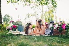 愉快的说谎在毯子的母亲和女儿户外在一个晴朗的夏天 库存照片