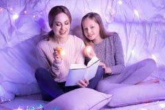 愉快的读书的母亲和女儿 图库摄影