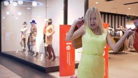 愉快的购物销售,跳进从享受的快乐的妇女折扣时尚商店,当购买时 股票视频