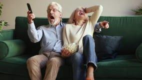 愉快的资深一起庆祝胜利的夫妇观看的体育电视比赛 影视素材