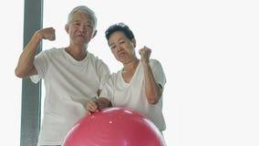 愉快的资深亚洲夫妇获得与健身房瑜伽球类的乐趣 免版税库存图片