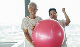 愉快的资深亚洲夫妇获得与健身房瑜伽球类的乐趣 免版税库存照片