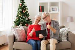 愉快的资深加上在圣诞节的片剂个人计算机 免版税库存图片