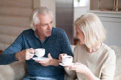 愉快的资深在长沙发谈话的夫妇饮用的茶 库存照片
