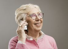 愉快的资深夫人谈话在电话 免版税图库摄影