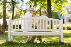 愉快的资深夫妇坐长凳在公园 库存照片