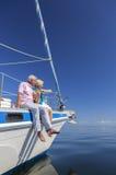 愉快的资深夫妇航行游艇或帆船 免版税库存图片
