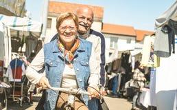 愉快的资深夫妇获得在自行车的乐趣在城市市场-在退休时间的活跃嬉戏的年长概念骑马自行车上 免版税库存照片